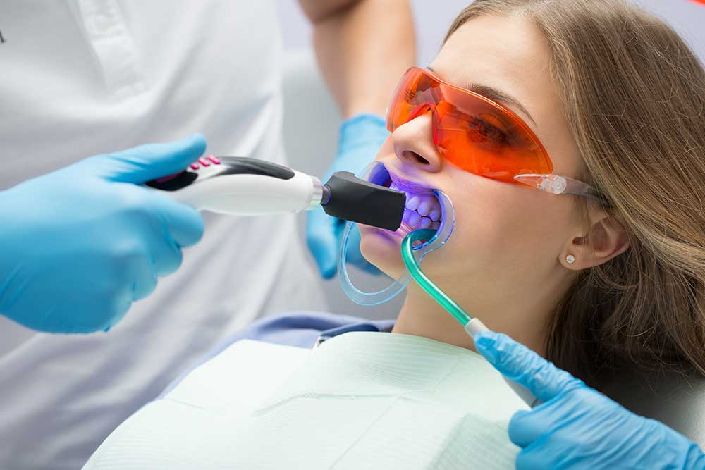Dental patient getting her professional teeth whitening treatment