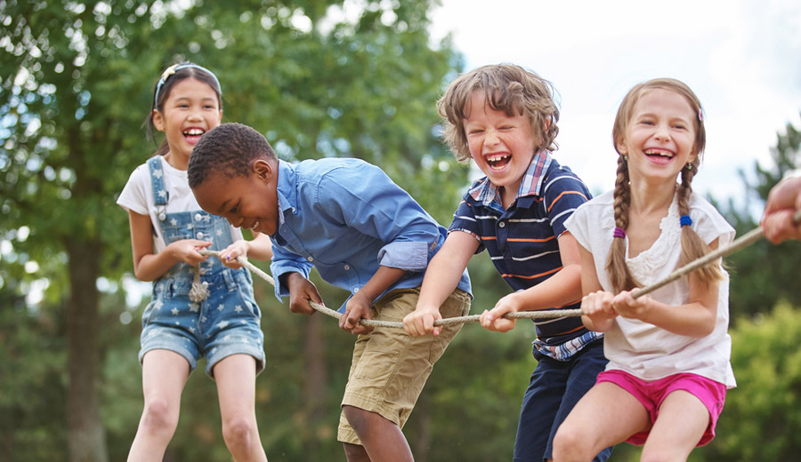 happy children playing tug of war