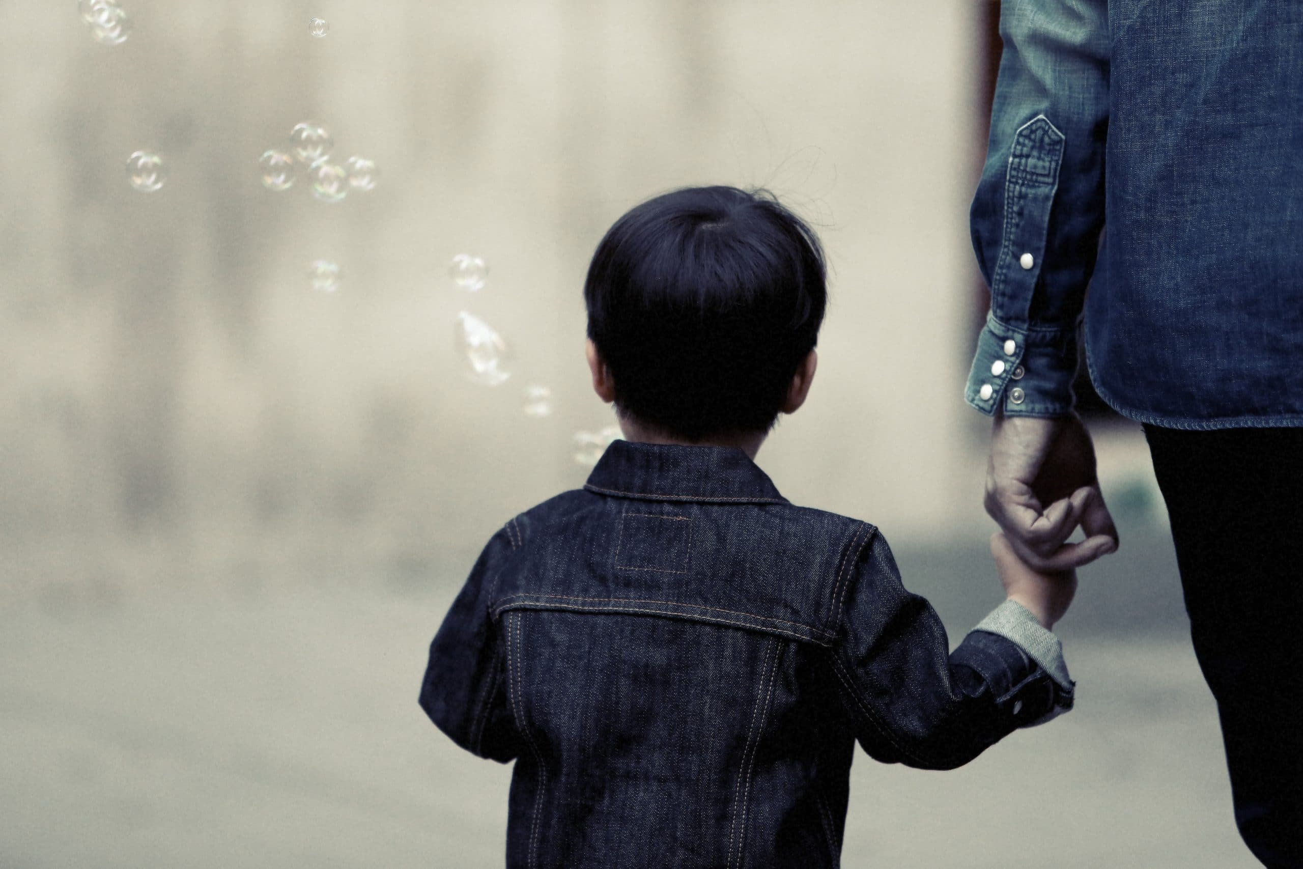 small child holding parent's hand
