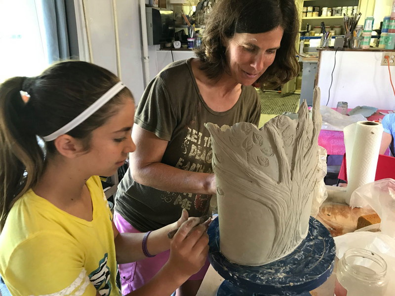 mother and daughter creating a ceramic vase in family pottery class