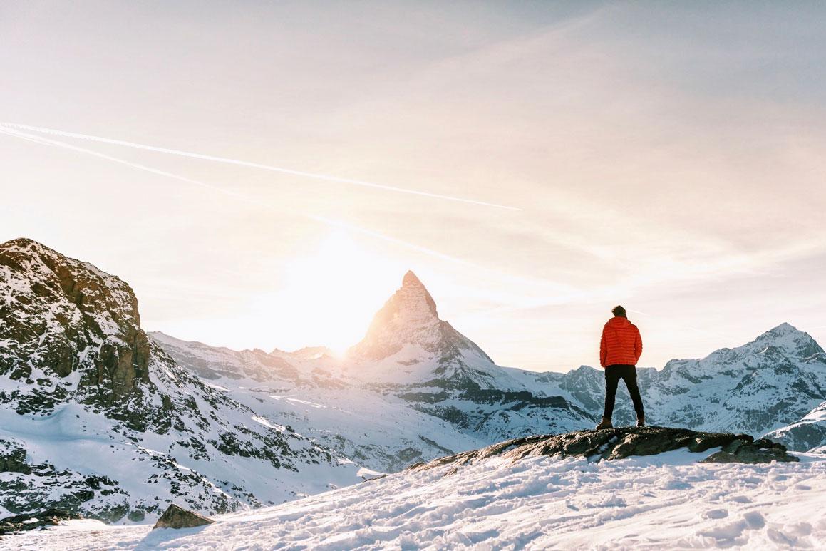 Man in orange jacket standing on a snowy mountain