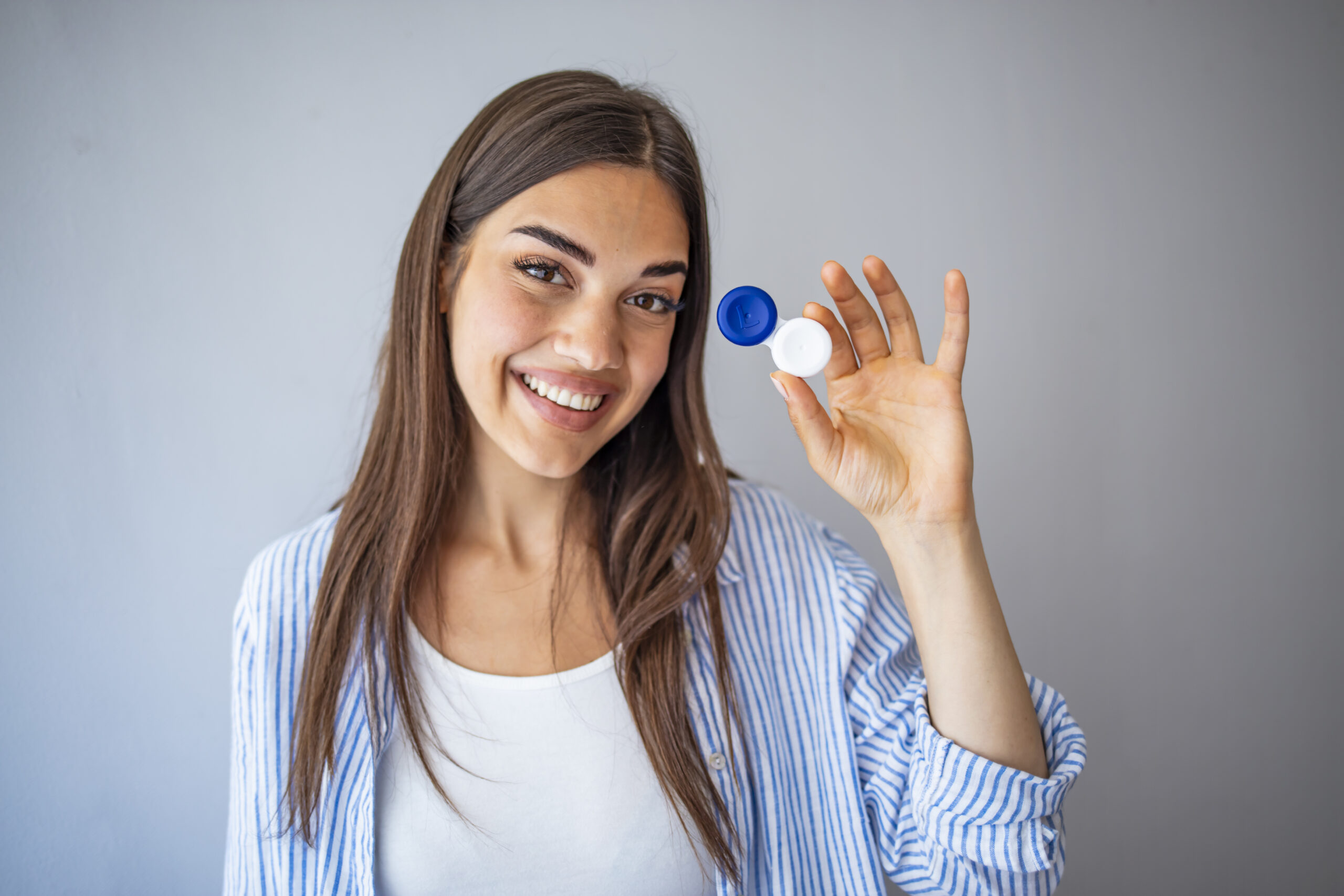 Woman  holding container for transparent soft contact lens. Young woman is preparing to insert lens in her eyes. Ophthalmic diseases and treatment. Poor vision concept.