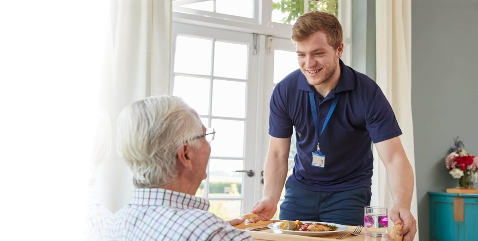 caregiver serving a food to senior man