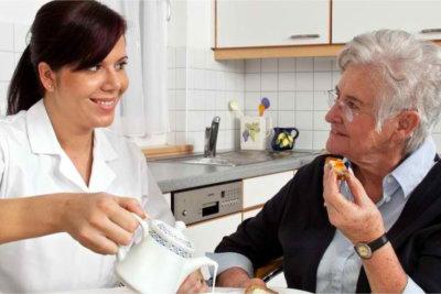 caregiver preparing meal for senior woman