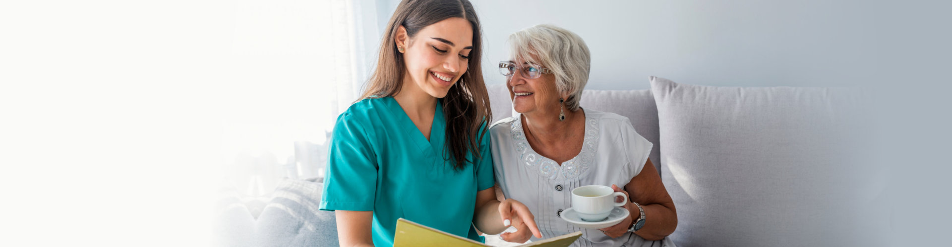 senior woman having a cup of tea with her caregiver