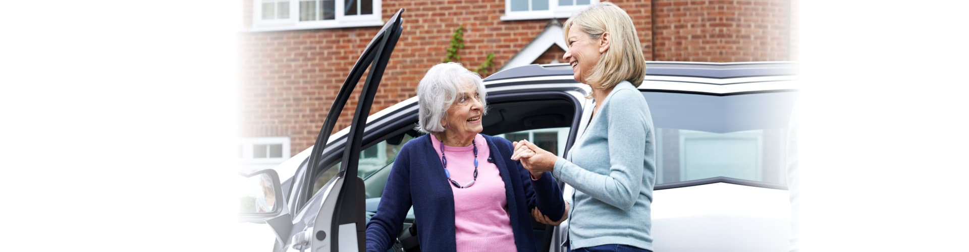 caregiver assisting senior woman to get out on the car