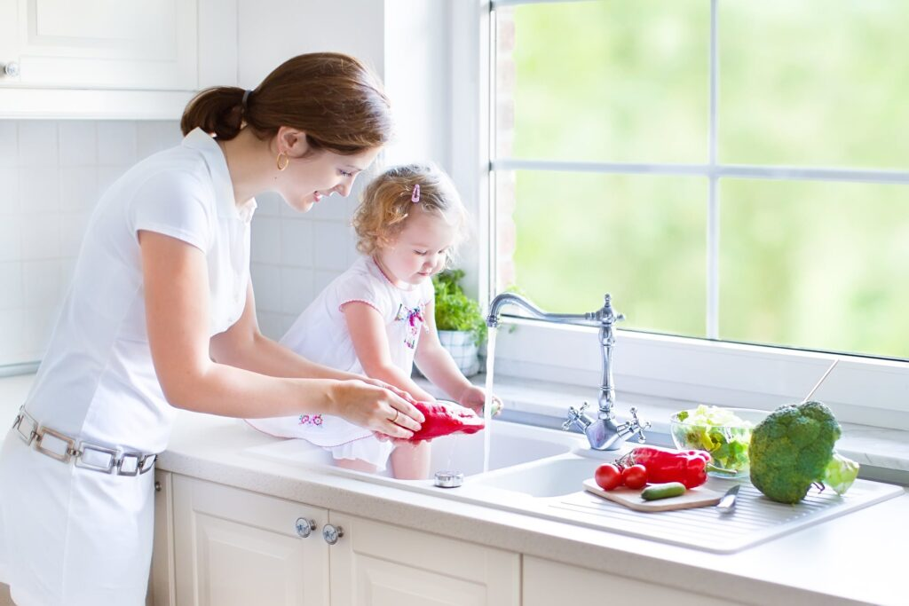 Mom and little girl washing vegetables in the sink.