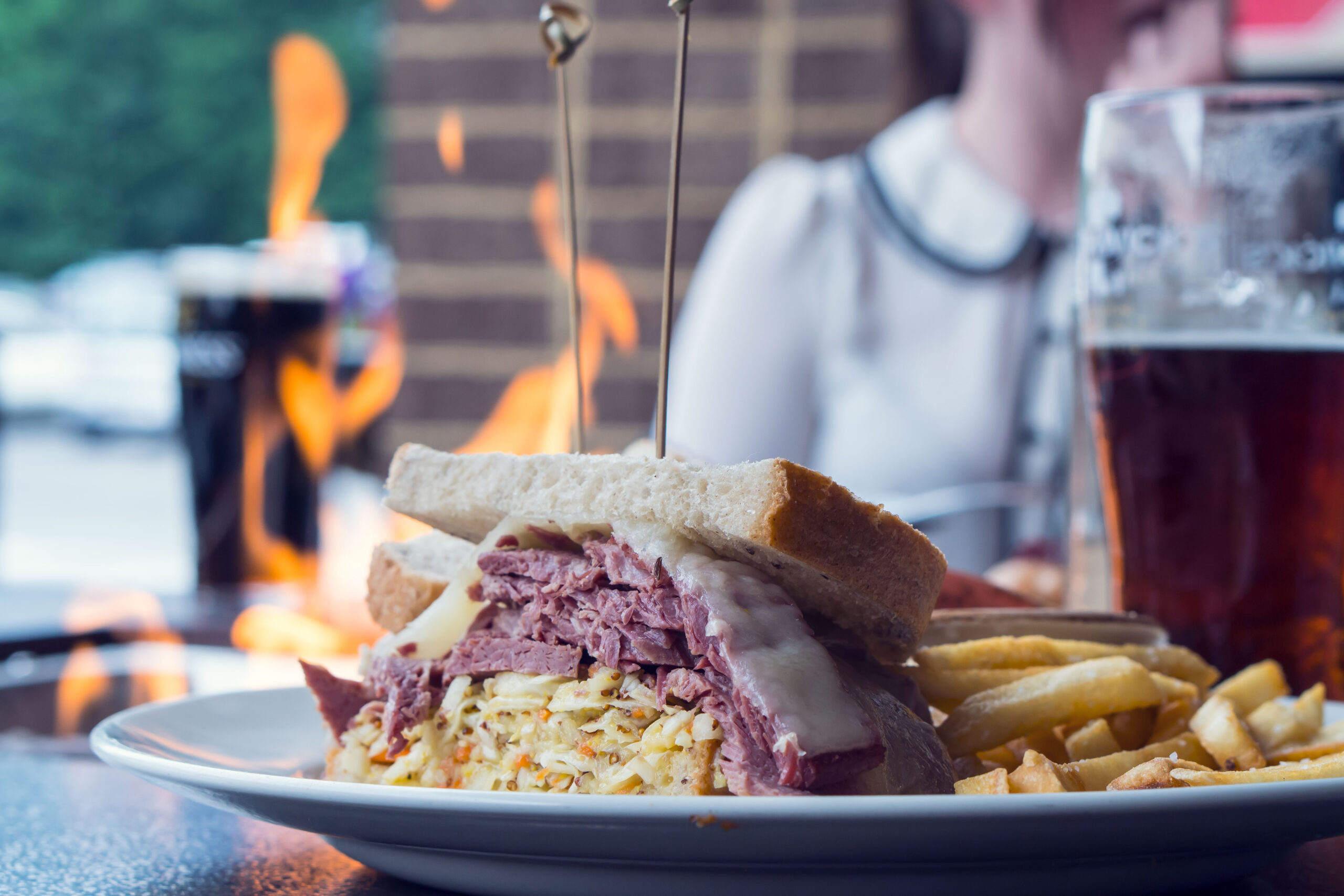 Corned beef sandwich with Smithwicks beer, at an outdoor firepit with female customer in background.