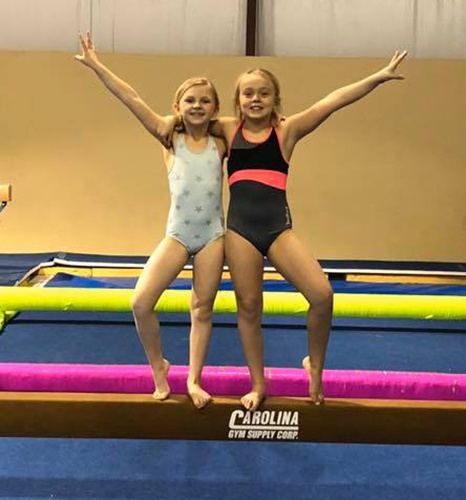 Two Girls posing on balance beam