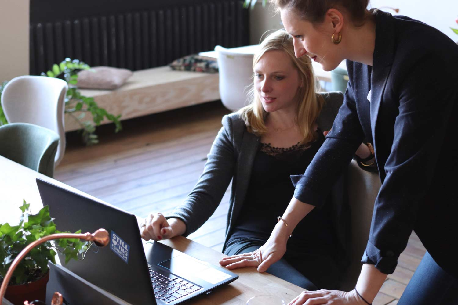 Two business-women discussing while one woman sits at a laptop and the other woman stands next to her and leans in to look at screen