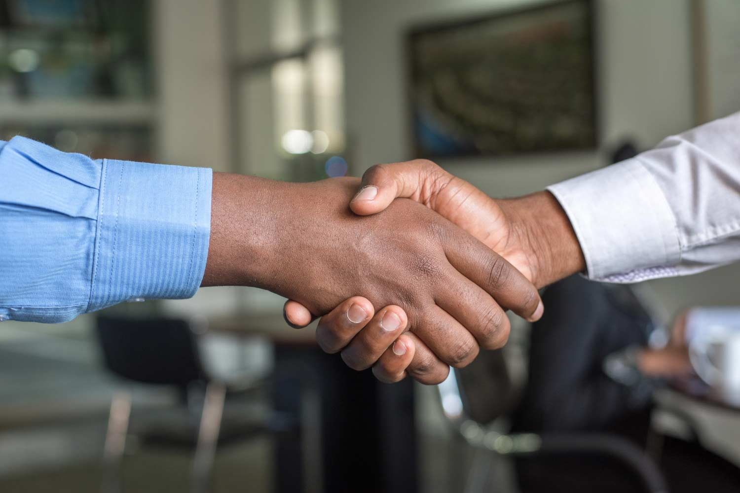 Close up (only their wrists & hands show) on two men wearing button-up shirts shaking hands with an office setup in the unfocused background