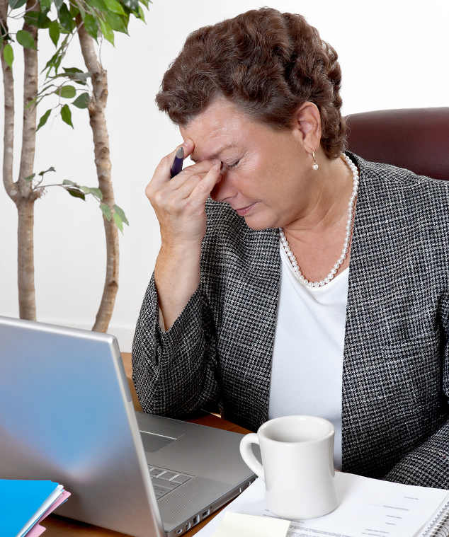 Mature business woman at her desk holding the bridge of her nose with a stressed expression