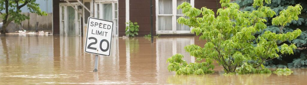 Flooded street with a house with flood insurance