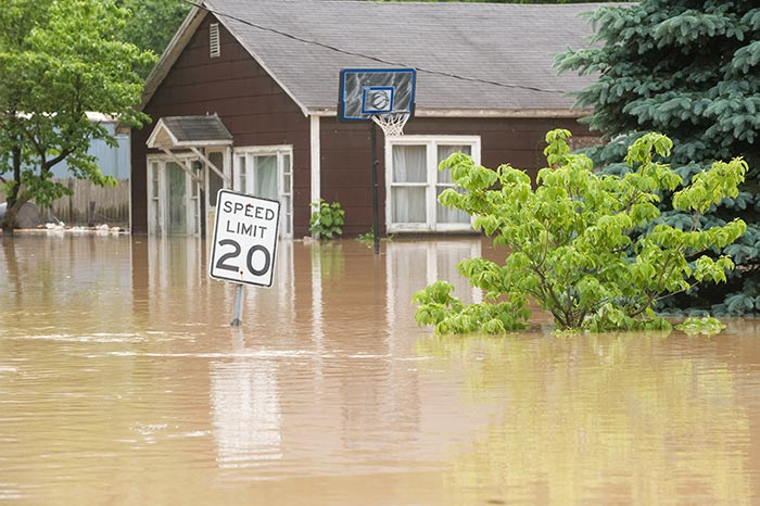 Flooded street with a house covered by flood insurance