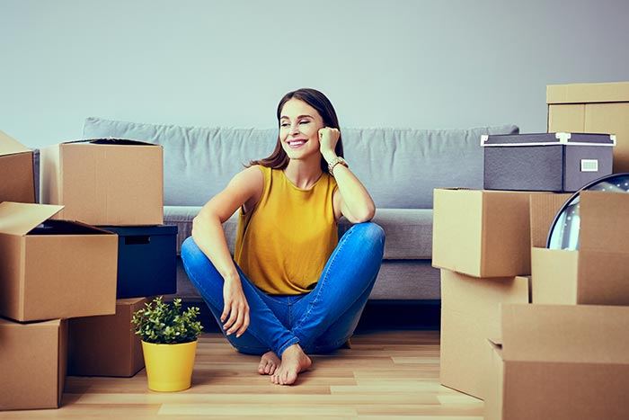 Women sitting in her new apartment covered by renter's insurance