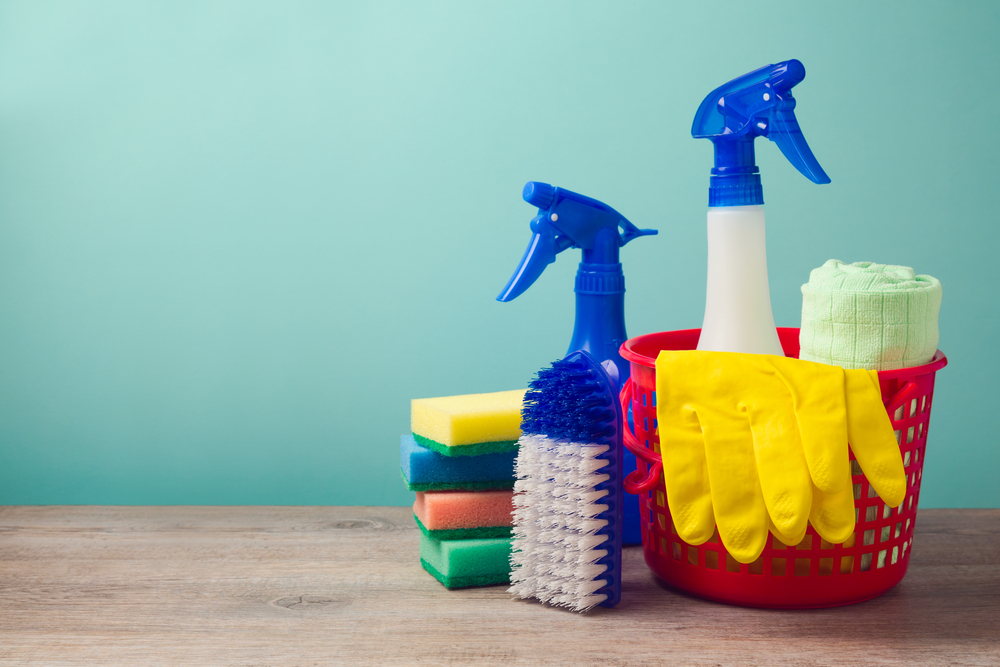 Several sponges, spray bottles, and disposable gloves are laid out on a table.