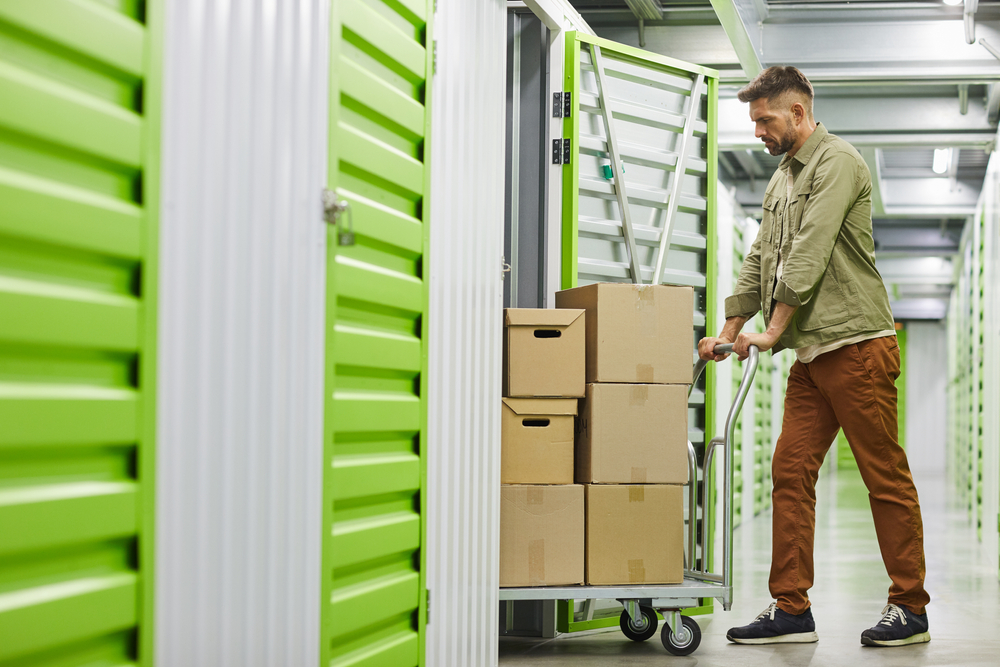 A bearded man in a teal shirt and brown pants moves a pile of boxes on a cart out of a storage unit. A closed unit with a green door can be seen closer to the camera.