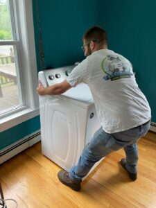 A man in a Trash Bandits shirt and jeans prepares to move a washing machine from a dark blue room.
