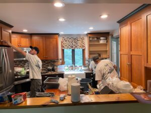 A view of a kitchen. Many drawers align the top of the room, a fridge is present on the left side, and cabinets on the right. Two workers clean the area and move things around.