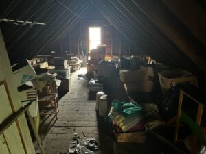 A full view of a house's attic. Several pieces of furniture, momentos and other various items litter the floor.