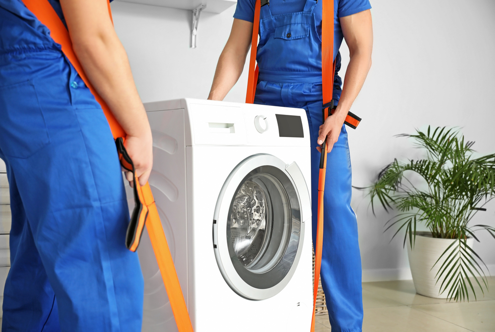 Two movers in all blue uniforms use orange belts to remove an old washing machine from a white room.
