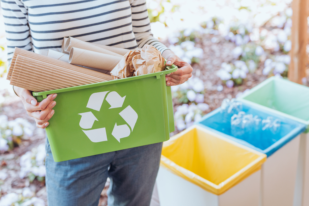 A woman stands next to multicolored trash cans with a green recycling bin filled with recyclable materials.