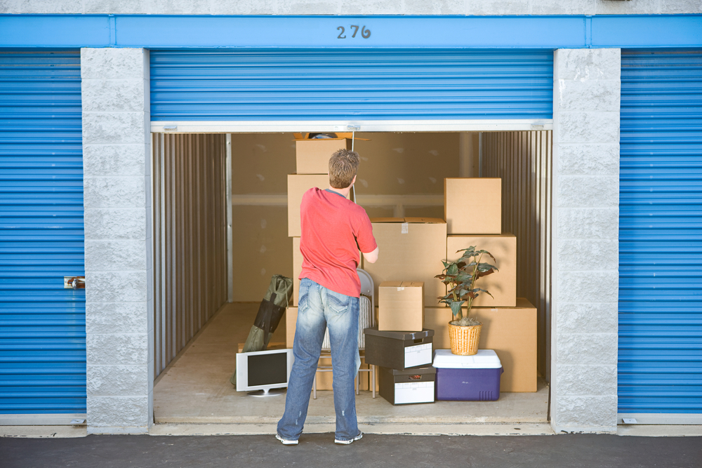 A man opens a blue garage door to reveal a storage unit with several stacks of boxes inside.