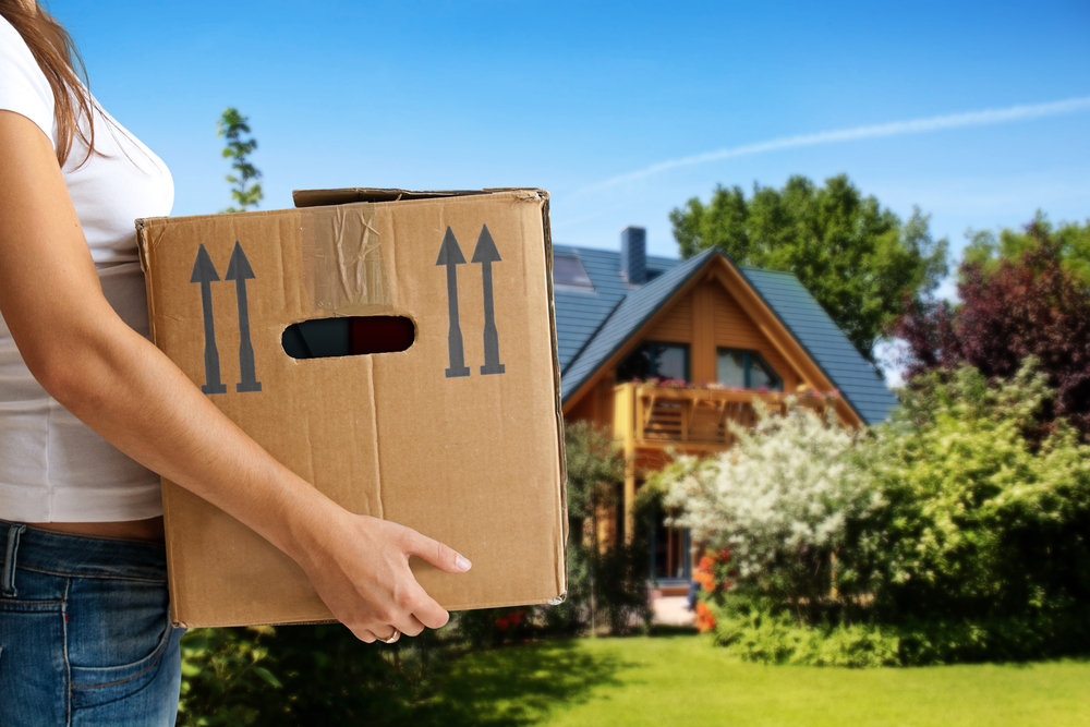 A woman holds a box with several upward facing arrows on it. In the background is a blurred out house and front yard.
