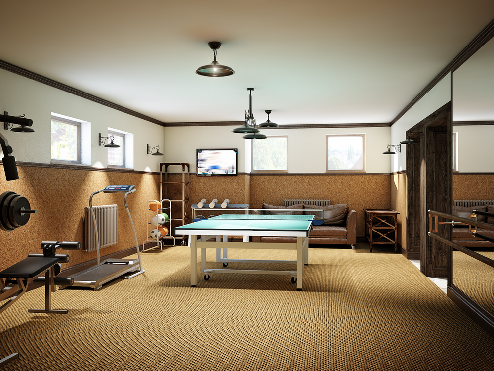 A remodeled basement that has been turned into a home gym. A ping pong table lies at the center of a room, surrounded by exercise machines and workout equipment