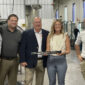 Watertown Mayor Emily McFarland holds one of the 300 million lawnmower blades made by Fisher Barton. McFarland was joined by, from left, Fisher Barton representatives: Jim Scott, chief operations officer; Lee Hermann, general manager; and Scott Hoffman, chief executive officer; and City of Watertown Strategic Initiatives and Development Coordinator Alex Allon.