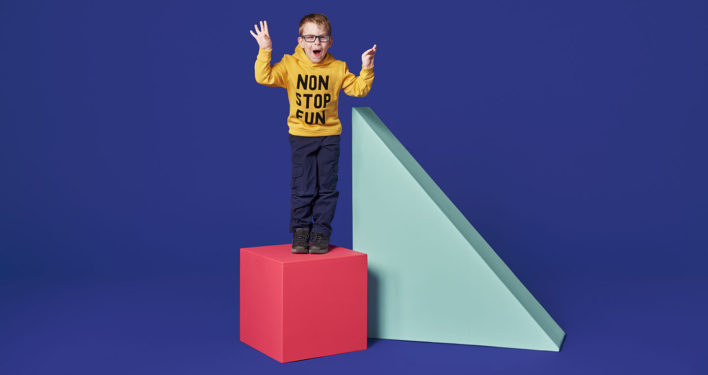 Child standing on a bright pink cube next to a large blue triangle against a purple background.