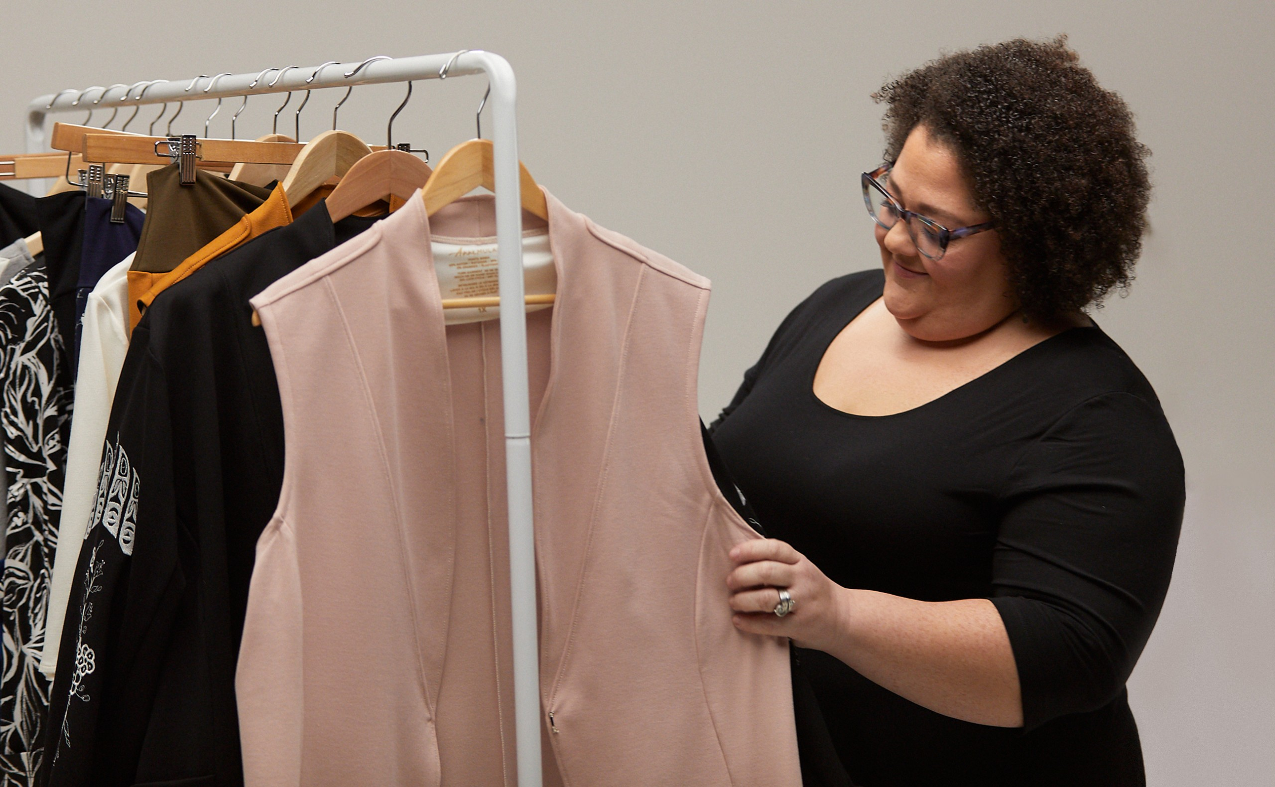 Woman browsing a clothing rack on the set of Anne Mulaire's video shoot.