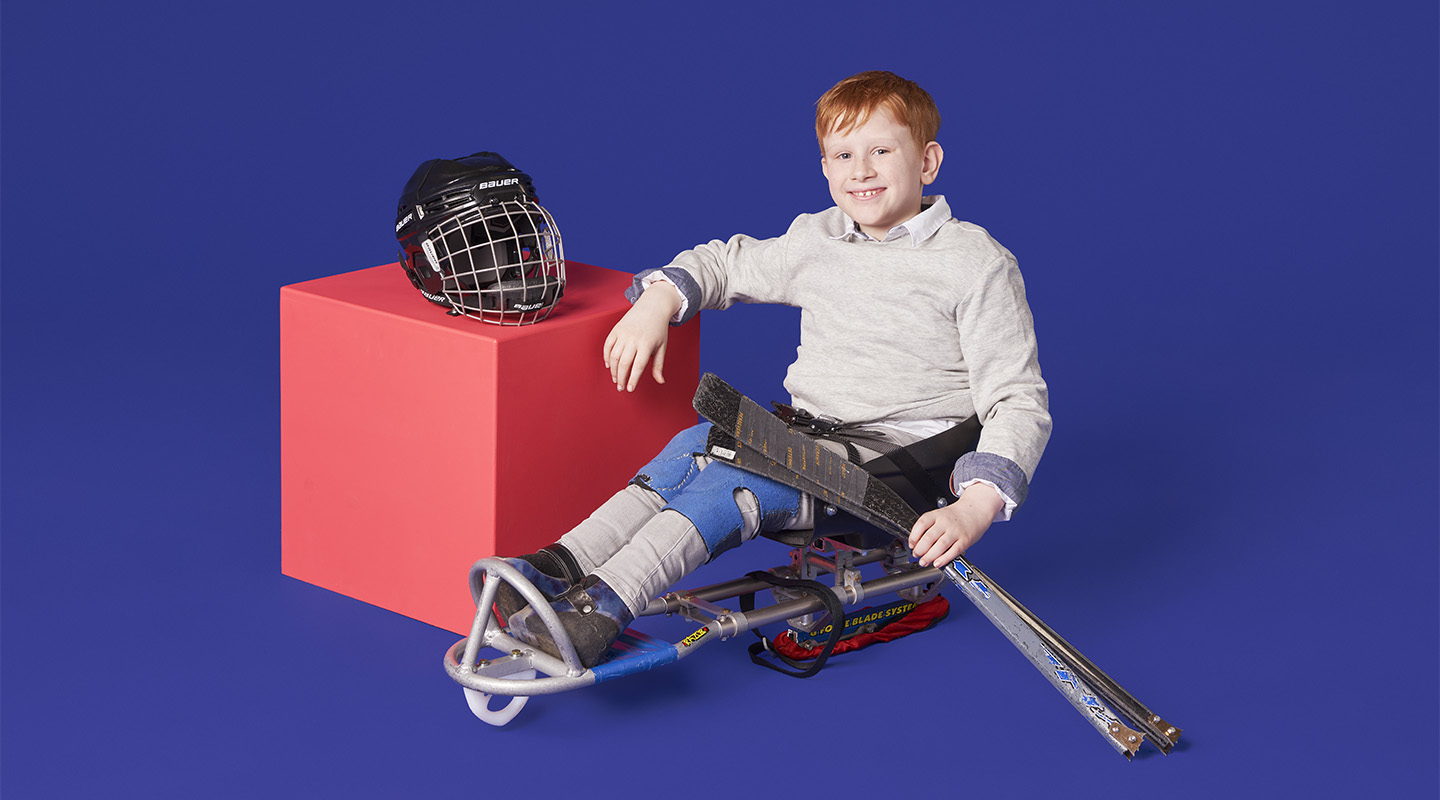 Still of a young sledge hockey player leaning against a vibrant pink cube on a purple background.