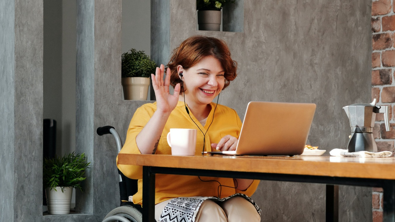 Happy employee waving at their laptop in an online meeting.