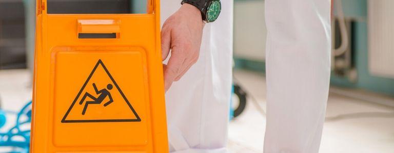 man holdling slippery when wet sign personal injury fargo