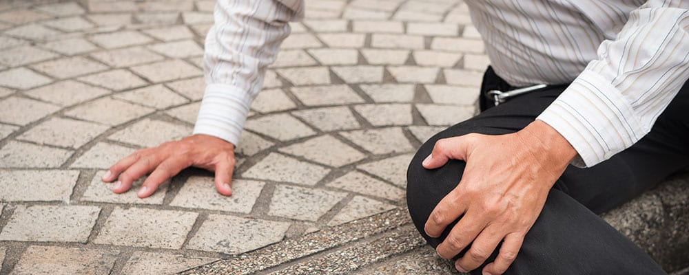 Slip and Fall Lawyer St Petersburg Florida - Photo of a man sitting on a curb holding his knee
