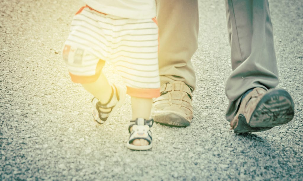 Blurred  of first steps of baby with father support , concept for toddler move