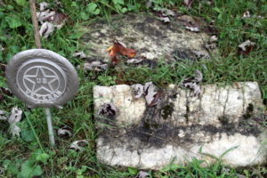 A headstone flush with the ground, no letters visible