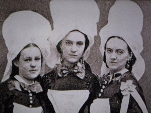 three women in tall white hats and black dresses