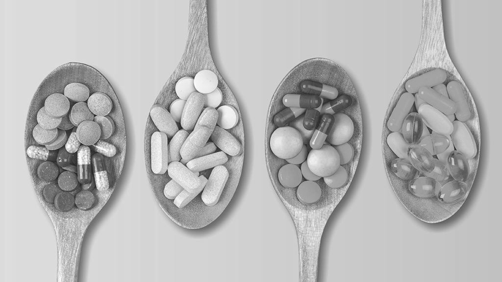 Vitamins Pills Dietary Supplements Nutraceuticals Nutritional Supplements on wooden spoon