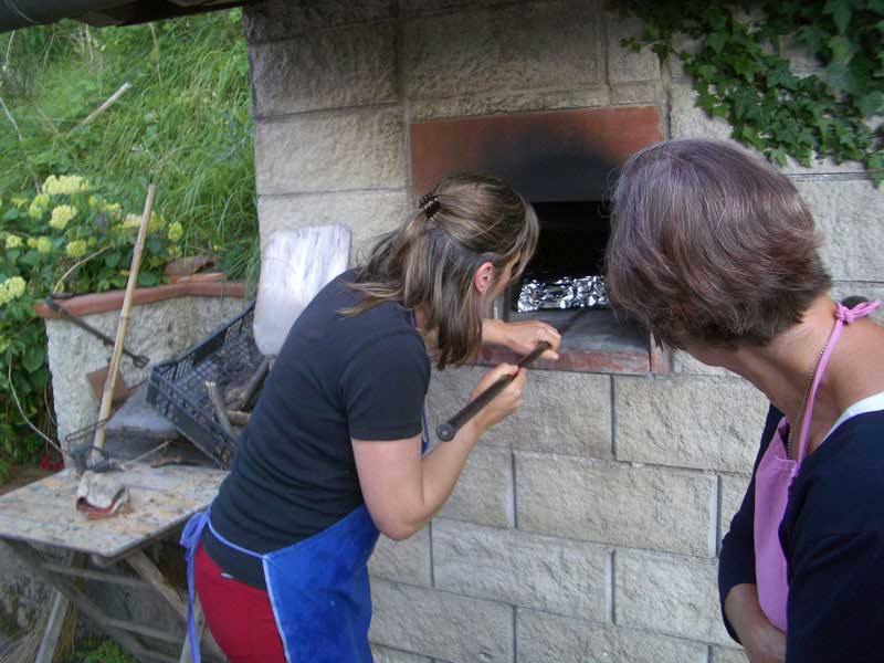 Gastvrouw Ella aan de pizza oven