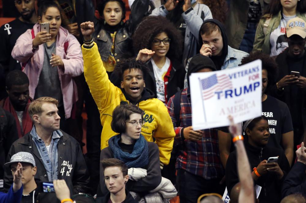 A protester raises his fist to supporters of Republican presidential candidate Donald Trump before a rally on the campus of the University of Illinois-Chicago.