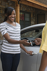 A young woman gets the keys to her car.