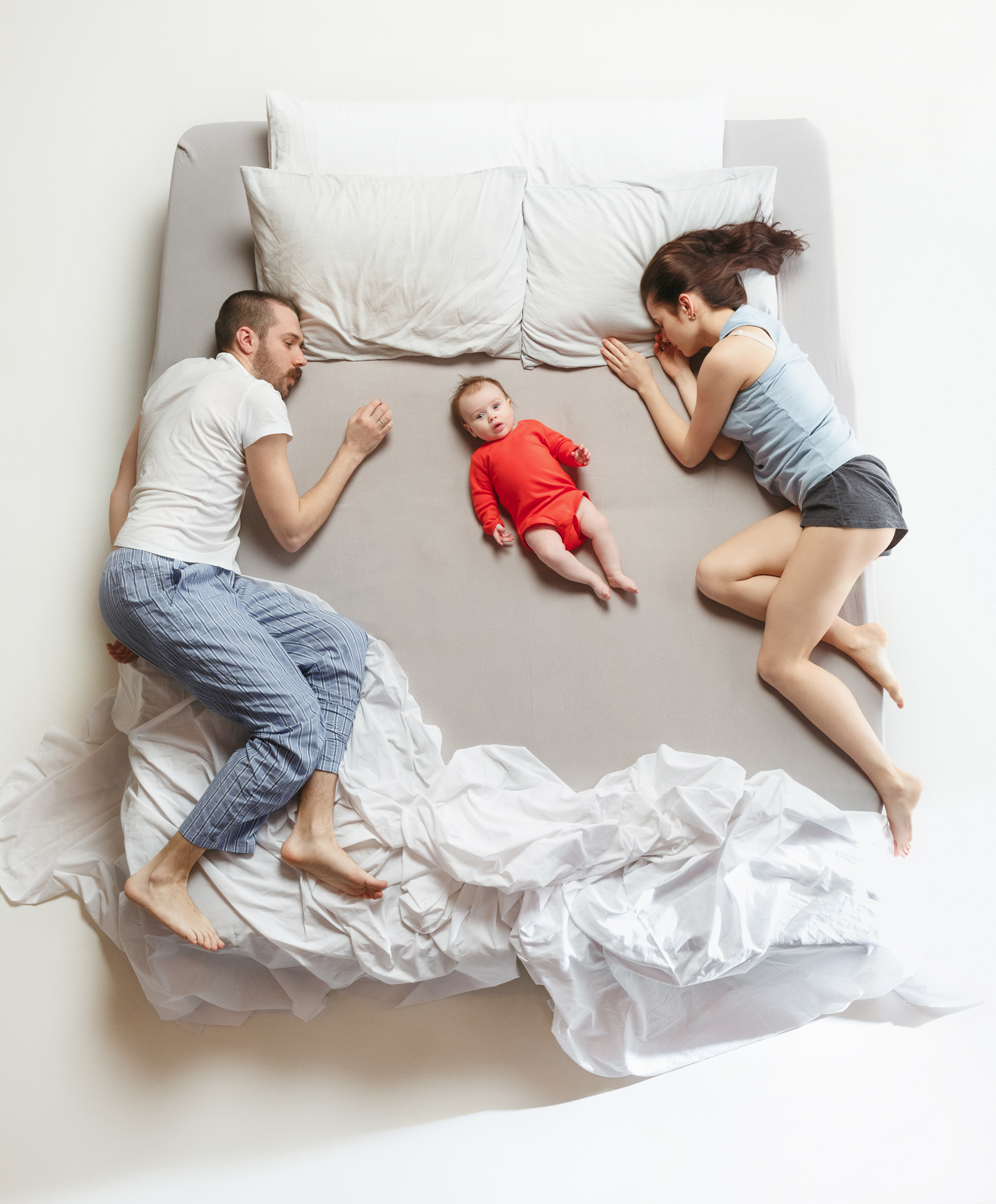 mom and dad in bed with baby