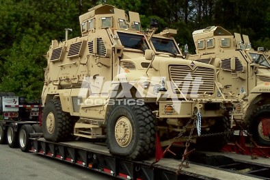 Military vehicle on double drop deck trailer