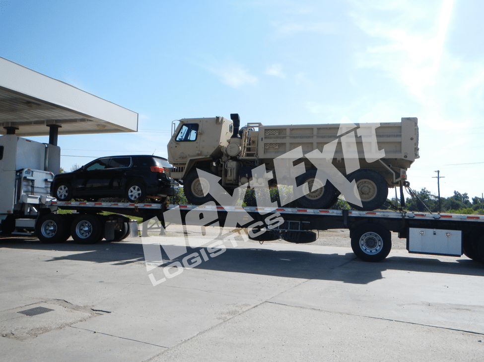 3 axle utility truck on flatbed trailer.