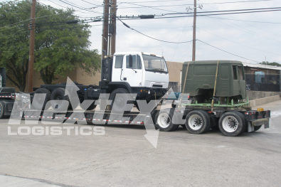 BAE Systems 3 axle utility truck and cab loaded on an extendable RGN trailer