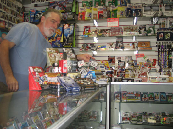 Ian behind the counter, helping a customer through their football offerings.