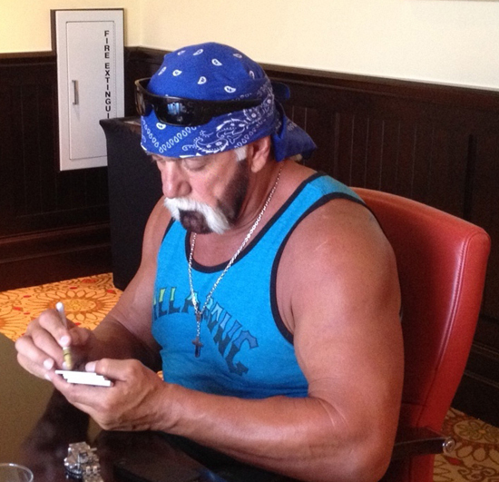 Hulk Hogan signs autograph cards for Upper Deck.